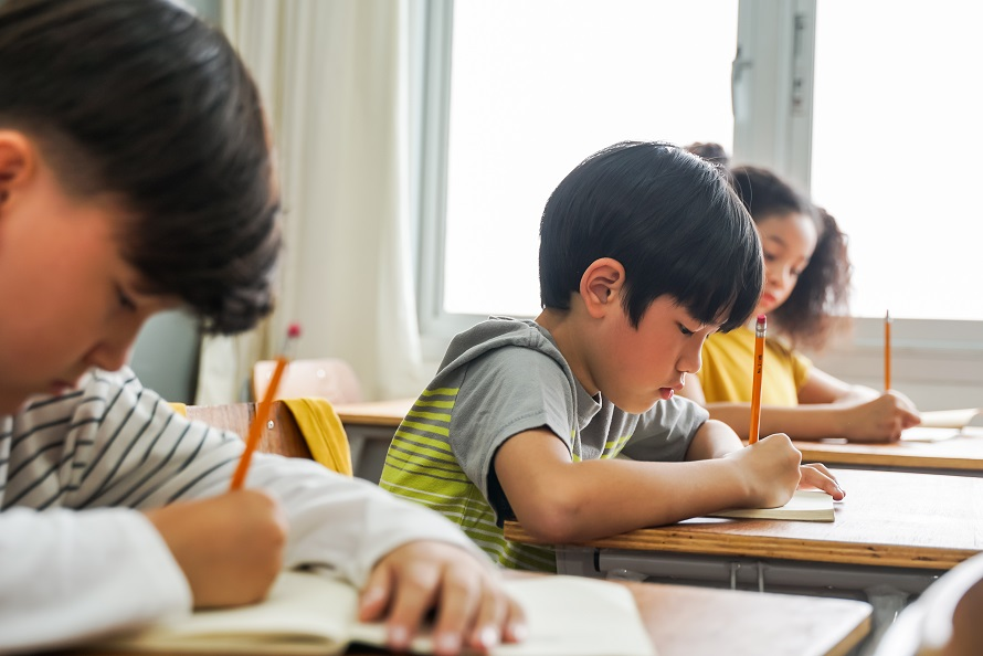 Asian school children sitting at desk in school writing in note book with pencil, studying, education, learning. Male and female students in classroom
