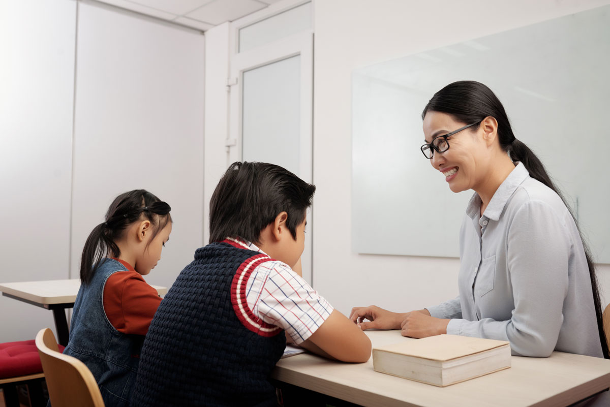 two asian kids sitting classroom smiling teacher glasses talking boy