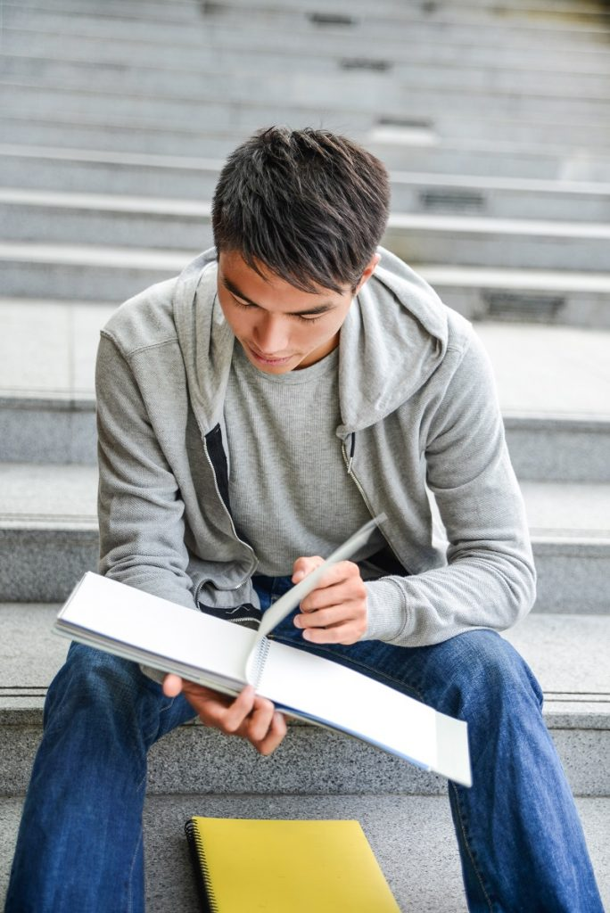 Happy smiling college student sitting holding book at college
