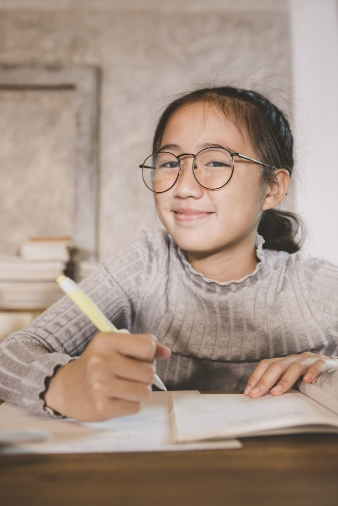 asian children wearing eye glasses with pen in hand studying in home living room
