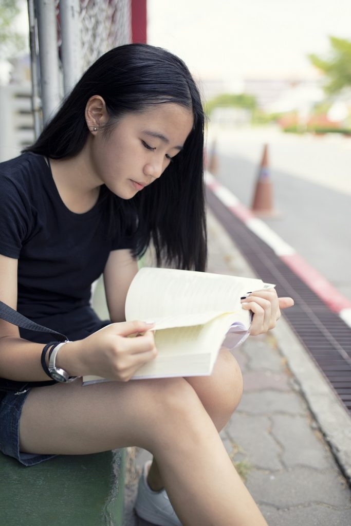 asian teenager reading book school street side
