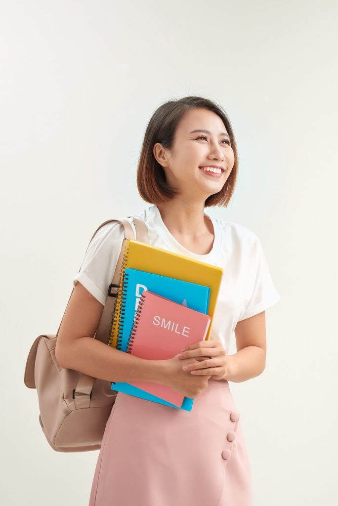 Young asian girl student with backpack hold books isolated on white background studio portrait
