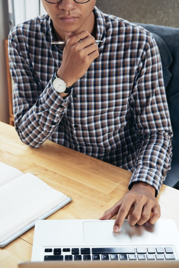 man in checked shirt sitting at table