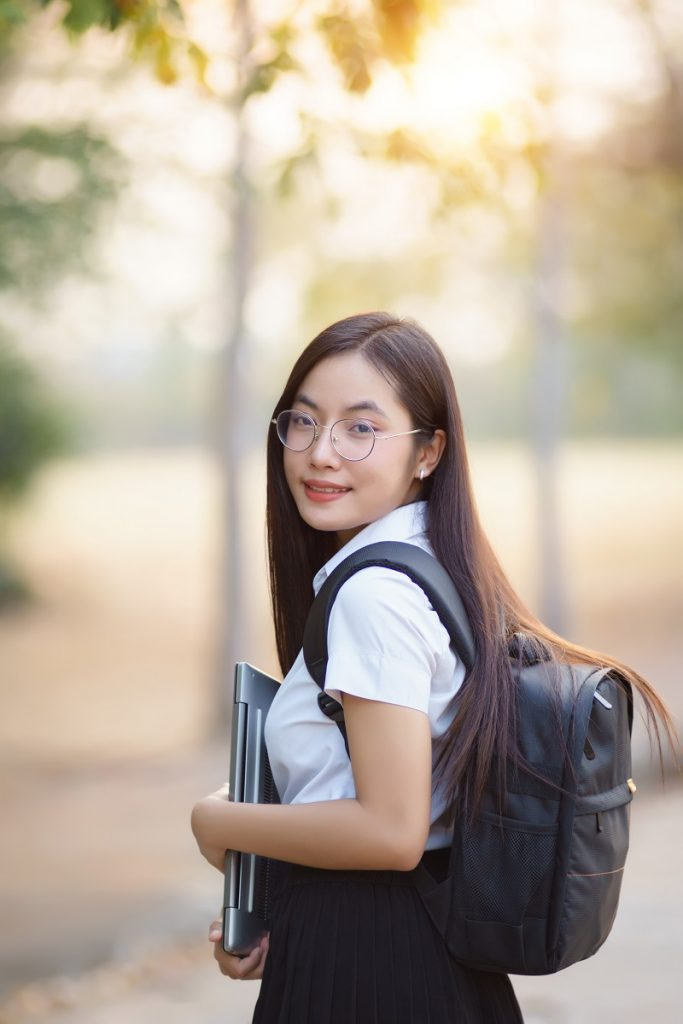 young female Asian university student carrying laptop