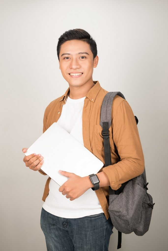 Portrait of Asian teenage college boy holding books