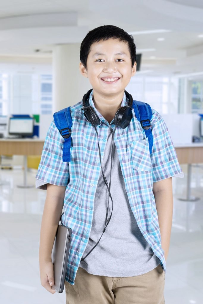 Handsome preteen student standing in the school