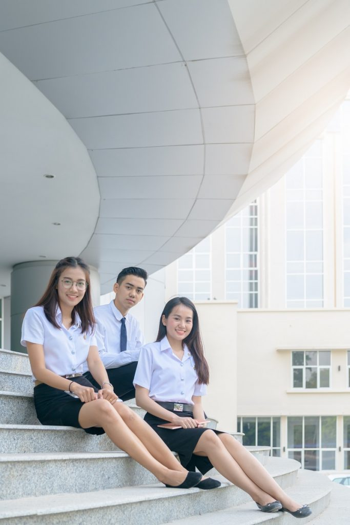 Happy asian students in uniform siting at university