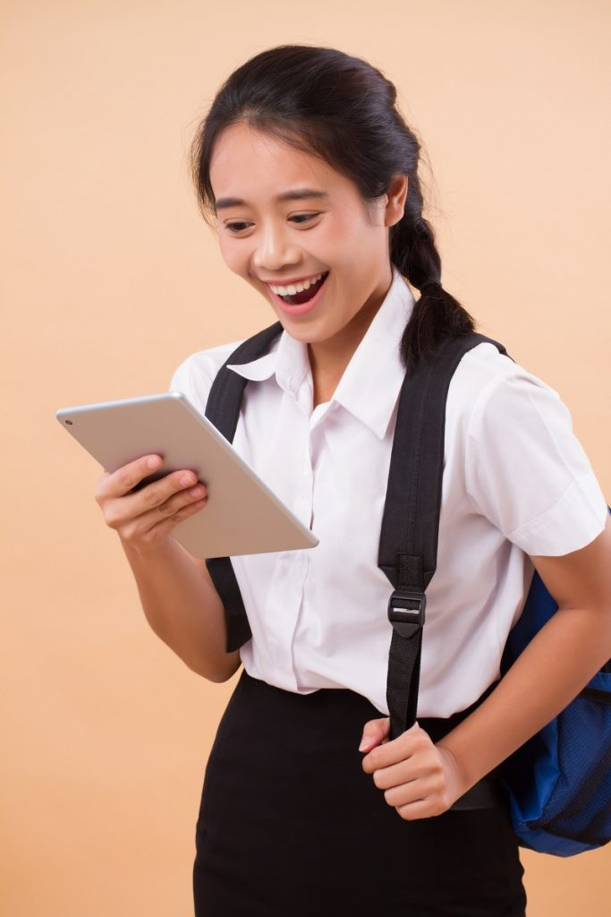 asian thai college woman student; education portrait of happy smiling college woman student carrying backpack, hand holding computer tablet; concept of college student education, university education
