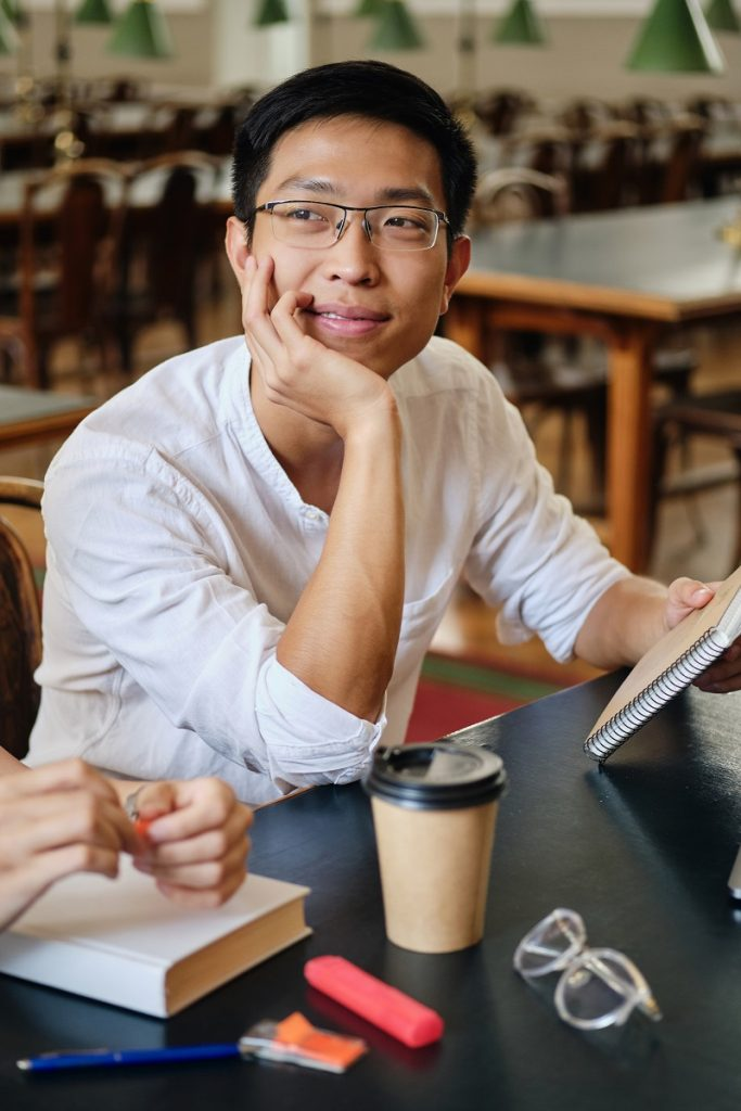 Young attractive asian student in eyeglasses dreamily studying in library of university