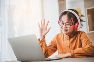Teenage Asian students in a yellow dress wearing a headphone are communicating through video conferencing for online learning. In a video conference call via apps. new normal concept.